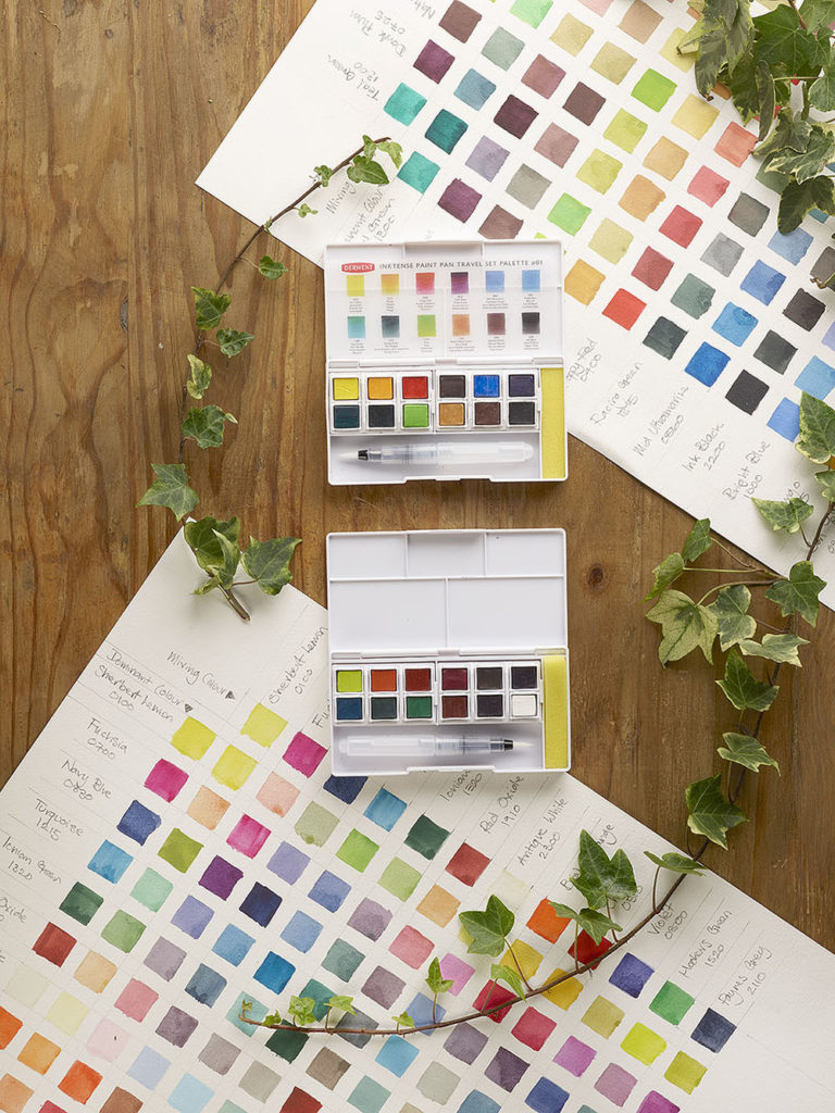 Derwent Inktense Paint Pan Travel Sets and colour mixing charts on wood background with ivy