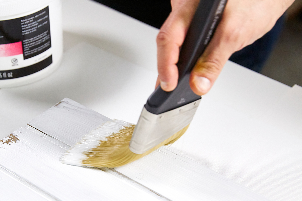 White Gesso being brushed onto a surface