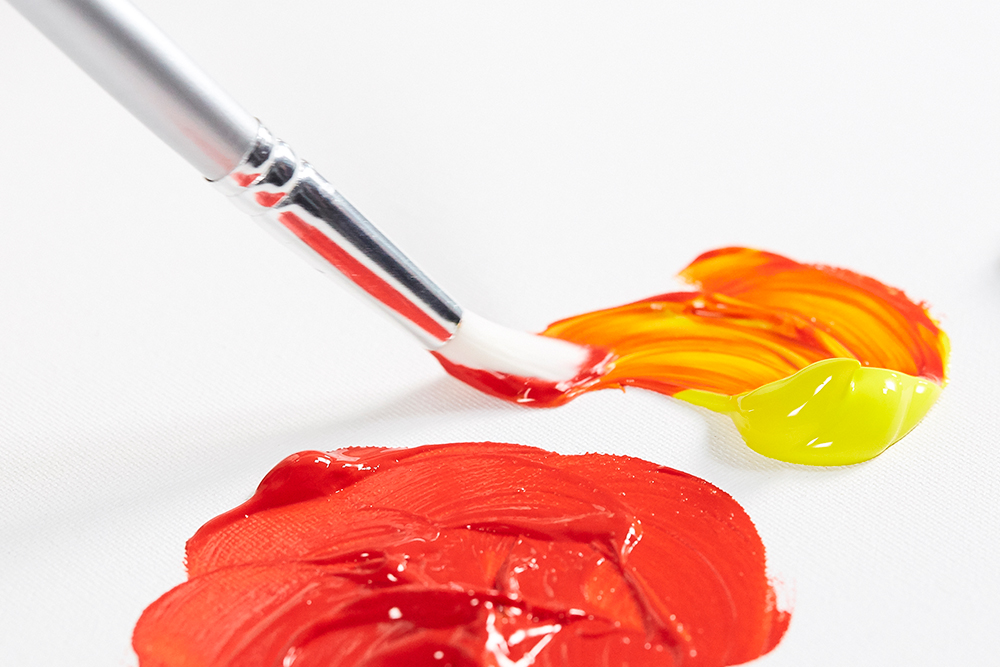 A synthetic artists paint brush being used to apply fluid acrylic colour