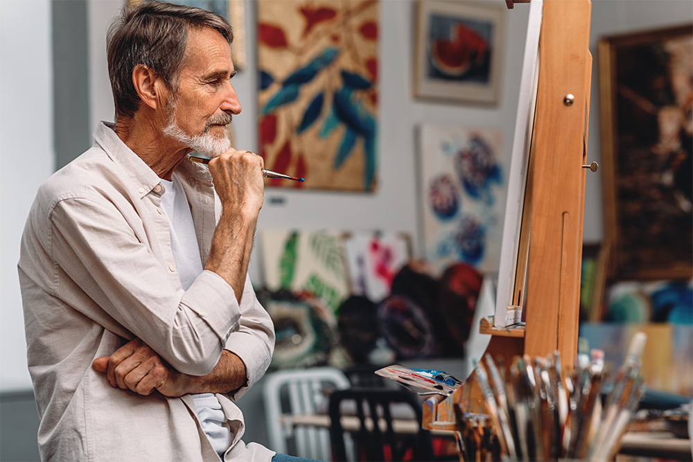 Side view of a thoughtful artist holding paintbrush while sitting in his studio