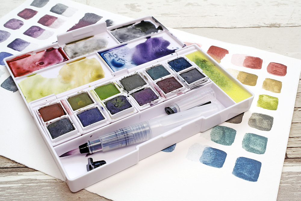 Derwent Graphitint Paint Pan Travel Set at angle with colour swatches