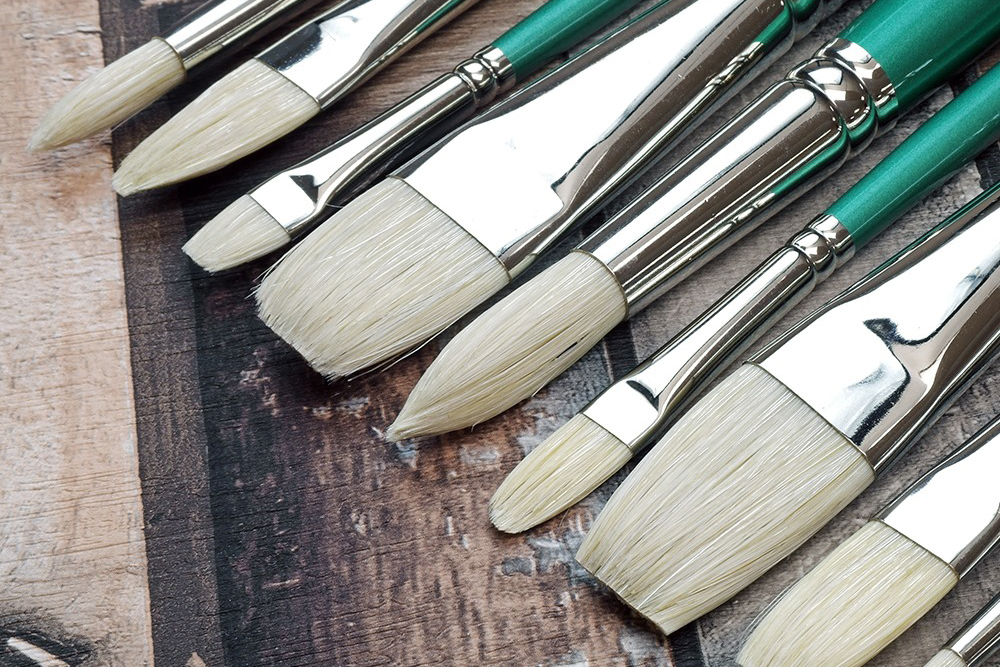 Pro Arte Series A Hog Brushes angled on a dark wooden background