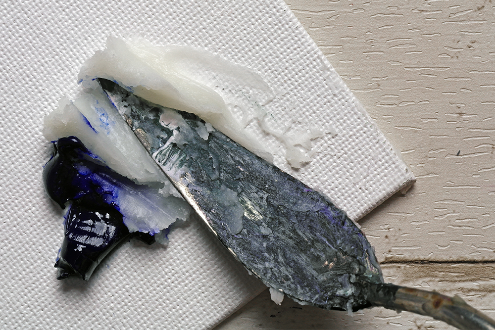 Zest It Cold Wax Painting Medium mixed with ultramarine oil paint with a painting knife on a white canvas board.