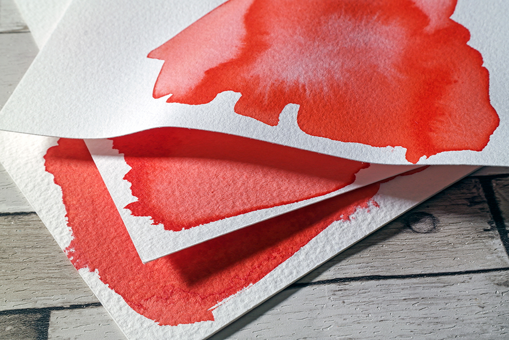 Assorted weights of paper painted with red acrylic ink