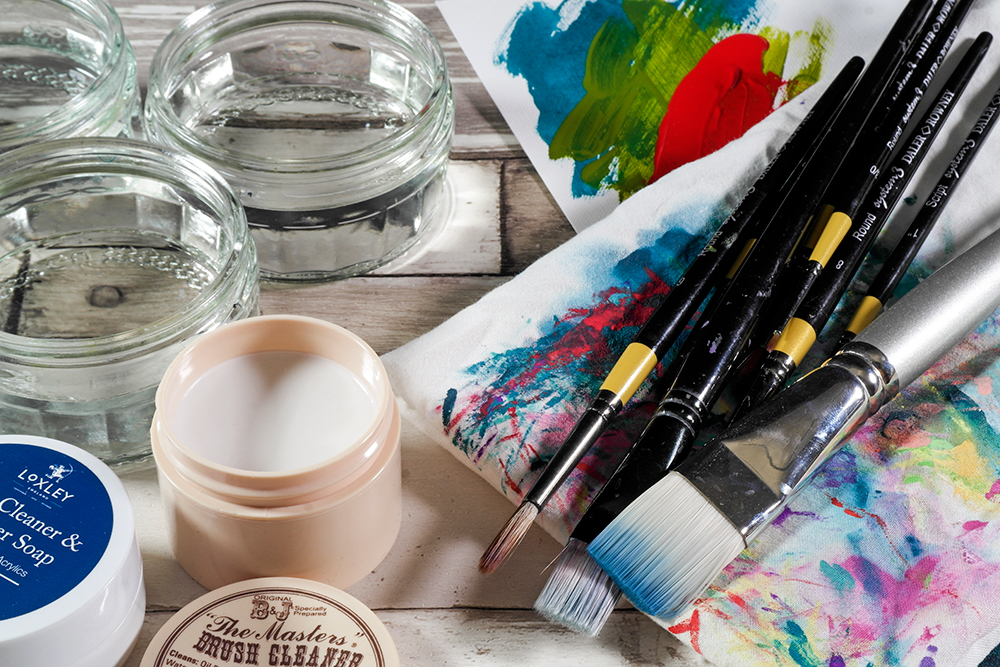 Assorted Acrylic Brushes on a paint rag with brush soaps and jars of water.
