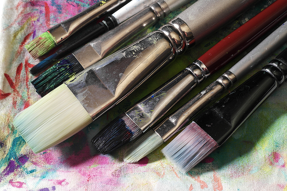 Assorted clean and dirty acrylic painting brushes on a painters rag.